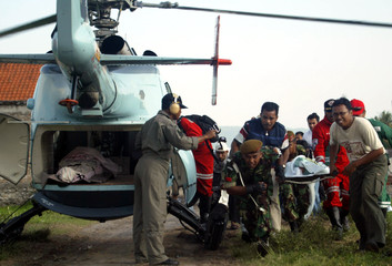 Rescue team carry injured earthquake victim to helicopter in Bantul