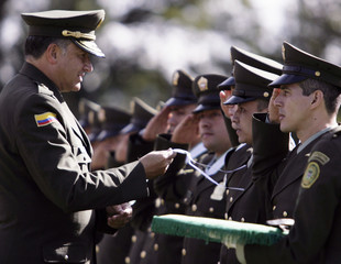 Police officer Juan Galicia is decorated by Police Chief General Oscar Naranjo during a ceremony at a police school in Sibate