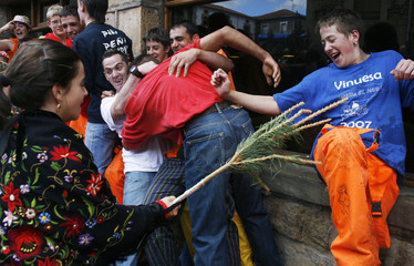 "A girl dressed as a ""pinorra"" hits young men with a pine branch during the Pinochada festival in northern Spain"