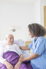 Reassuring confident african female doctor visiting elderly caucasian patient in hospital bed