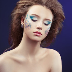 Fashion beauty portrait of a beautiful girl with creative make-up with patterns on a blue background.