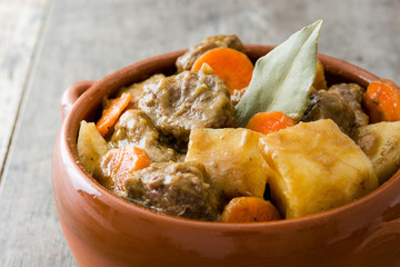 Beef meat stewed with potatoes, carrots and spices in bowl on wooden table