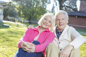Elderly couple enjoying summer sunset relaxing on garden grass