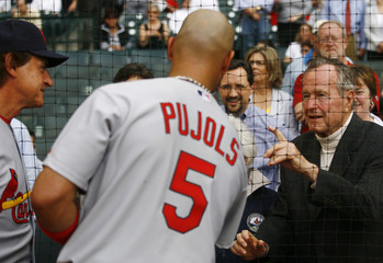 Former US President Bush greets Cardinals' LaRussa and Pujols before MLB National League baseball home opener against the Astros in Houston