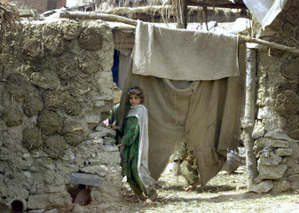 AFGHAN CHILD STANDS OUTSIDE HER HUT WHERE MANY AFGHAN REFUGEES LIVES INISLAMABAD.