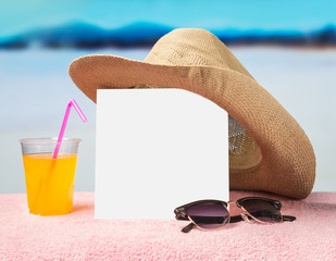 Summer sale or offer background for advertising. White square card on towel with sunglasses, yellow cocktail and hat. Free blank copy space for text and content. Blurred holiday paradise in the back.