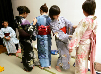 Japanese women have kimono fitters dress them up in traditional yukatas in Tokyo.
