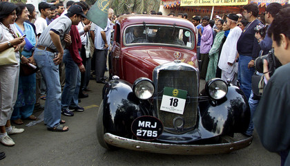 A CONTESTANT STEERS HIS 1937 MERCEDES BENZ THROUGH SPECTATORS DURING AVINTAGE CAR RALLY IN BOMBAY.