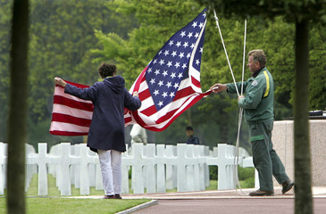 File photo of the Stars and Stripes being lowered at sunset at American war cemetary in Colleville-sur-mer