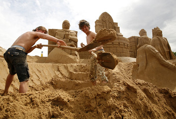Artists work on sculpture during Sand Sculpture Festival in Travemuende