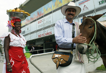 Women selling fruit stands next to man dressed up as Valdez, Colombian icon to represent Colombian coffee farmer, at entrance of Plaza Mayor convention center in Medellin