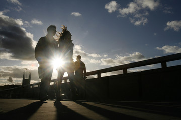 A couple are seen silhouetted as they cross London Bridge