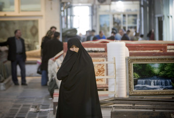 A woman looks on as she stands in Tehran's Grand Bazaar