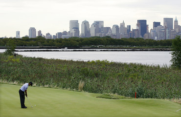 New York's lower Manhattan skyline is seen in the background as Tiger Woods from the U.S. putts on the 14th hole during first round play at the Barclays golf tournament