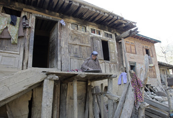 A Kashmiri woman sits at her house in the village of Bathi-Jalan