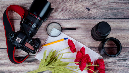DSLR camera, on a wooden background with a bouquet of red poppies and a notepad for recording
