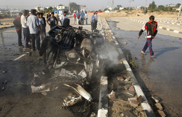 Palestinians stand near destroyed vehicle after hit by missiles in Gaza