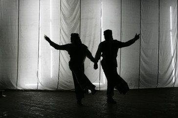 Members of Iraqi national folklore dancing troupe are silhouetted behind a curtain before the start of a dance and act play in Baghdad