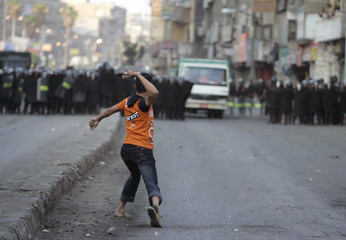 A Protestor throws something towards riot police during clashes in Mahalla City