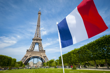 French tricolor flag flying in blue sky in front of the Eiffel Tower in Paris, France
