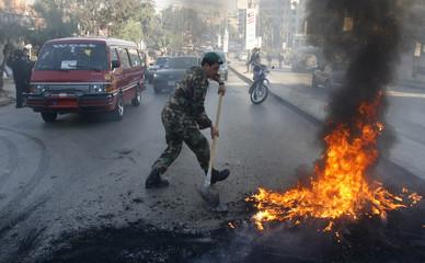 A Lebanese soldier tries to extinguish tyres set on fire by Shi'ite Muslims to cut off the main road to Beirut's Hezbollah-controlled suburbs