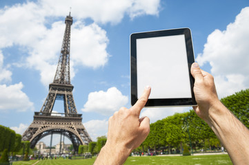 Hands holding a blank tablet in front of a bright view of the Eiffel Tower in Paris, France