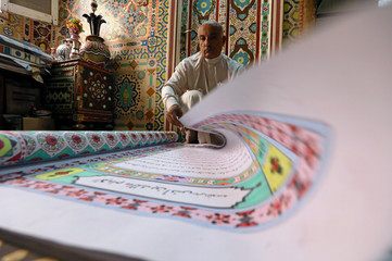 Saad Mohammed turns the page of a book he's handwritten at his studio in the town of Belqina
