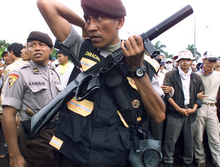 A MEMBER OF THE INDONESIAN MOBILE POLICE BRIGADE HOLDS A TEARGAS LOUNCER DURING A PROTEST IN JAKARTA.