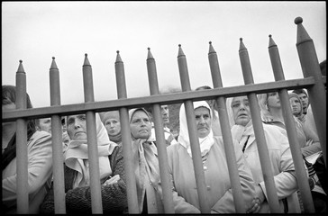 Bosnian Muslim women look through the bars in a cemetary in Srebrenica