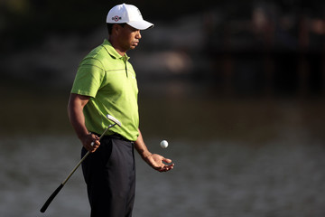 Tiger Woods bounces a ball on his golf club as he plays on the 18th hole during the HSBC Champions golf tournament in Shanghai