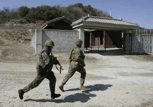 Marines from the U.S. and South Korea equipped with MILES run past a house during a military operation in Pocheon