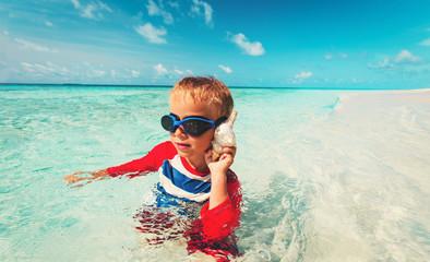 little boy listening to seashell on beach