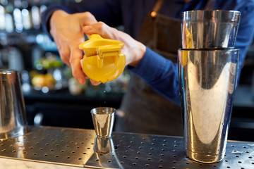 bartender squeezing juice into jigger at bar