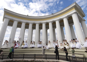 Women in bridal gowns pose for pictures during a parade of newly wed brides in Odessa