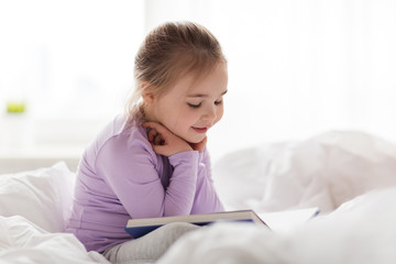 happy little girl reading book in bed at home