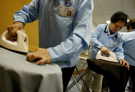 JOBLESS LEARN TO IRON CLOTHES UNDER RETRAINING SCHEME IN HONG KONG.