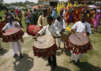 Tribal men play musical instruments during a mass marriage ceremony at Salbari village