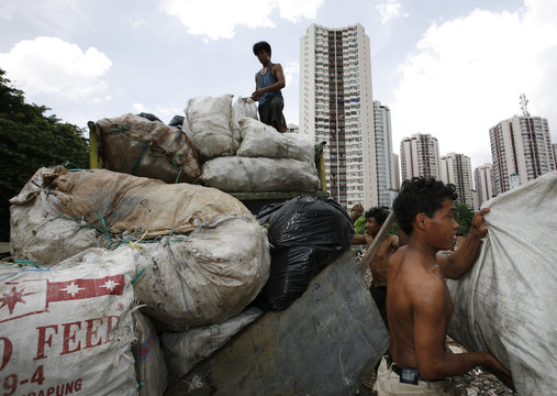 Workers load plastic for recycling onto a truck near luxury apartments in Jakarta
