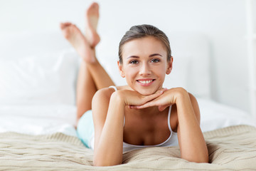 beautiful happy young woman lying on bed at home