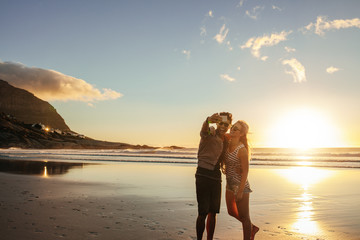 Happy young couple taking self portrait at beach