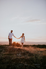 couple holding hands with sunset