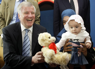 Seehofer, Bavarian state premier and leader of the CSU, gives a teddy bear to a six-month-old Palestinian girl Elrub and her mother Khitam, in a Munich hospital