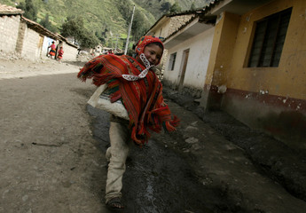 Andean boy in traditional Inca clothes runs to school in village of Huilloc in Cuzco