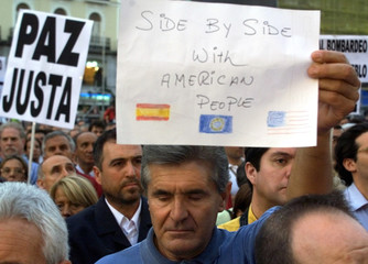 MAN IN MADRID HOLDS PLACARD DURING MOMENT OF SILENCE FOR VICTIMS OFATTACK IN USA.