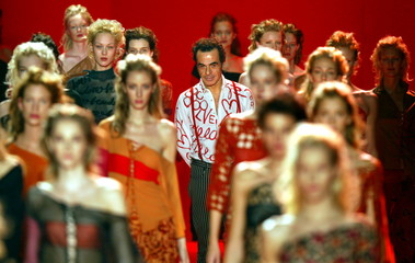 Italian designer Romeo Gigli (C) appears on the catwalk between models after his Spring-Summer ready..