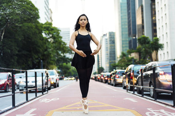 Brazil, Sao Paulo, Ballet dancer standing on tiptoes on bicycle lane