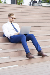 Handsome young businessman working on laptop sitting on the stairs outdoor