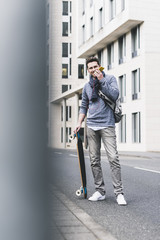 Businessman carrying skateboard, using smartphone and earphones