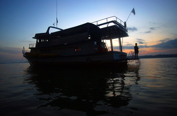 Environmentalist stands alone on empty tour boat in Phang Nga Bay in Thailand.