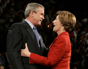 U.S. President George W. Bush embraces first lady Laura Bush at an election rally in Dallas, Novembe..